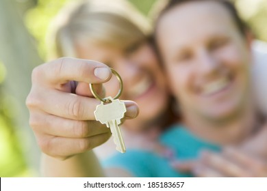 Happy Couple Holding Blank House Key Outside with Room For Your Own Text On The Key.
