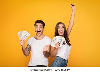 Happy couple holding bunch of money banknotes and celebrating success over yellow background