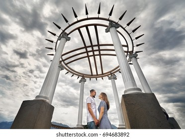 Happy couple holding by hands in the house with roof in shape of Shanyrak, Kazakh symbol of family in the famous park of Almaty, Kazakhstan