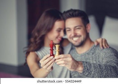 Happy couple holding chess figures, black king, white queen