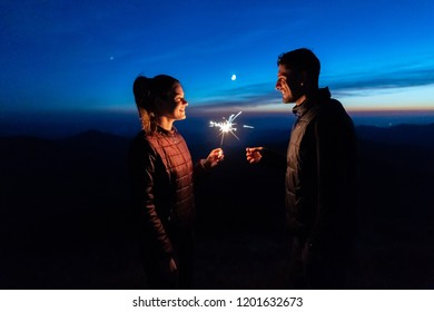 The happy couple holding firework sticks on the mountain background