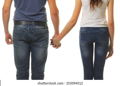 Happy couple holding hands. Closeup of young affectionate couple holding hands over white background.