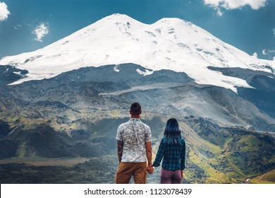 Happy couple holding hands and enjoying the view of Mount Elbrus, rear view. Travel Holiday Destination Concept