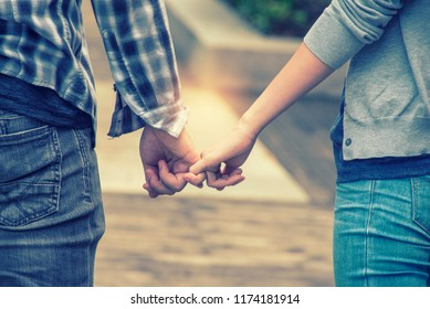 Happy couple holding hands and in love walking in the autumn park.