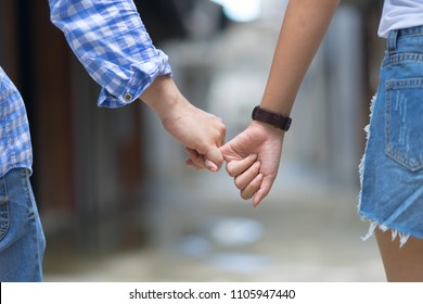 Happy couple holding hands pinky promise or pinky swear.Man woman in love trust and support togetherFemale and male hands together romance relationship feeling love romantic conceptual.