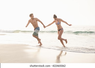 Happy couple holding hands and running on the beach