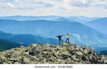Happy couple holding hands up, standing on top of cliff, beautiful mountains scenery on background. Hiking, tourists reaching peak together. Wild nature with amazing views. Sport tourism concept.