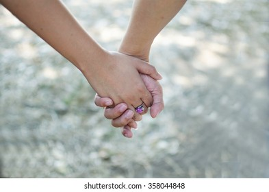 Happy couple holding hands.focus on hands.