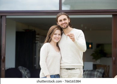 Happy couple holding keys standing against new own modern residential house, smiling young homeowners man and woman embracing looking at camera after buying rental real estate, mortgage loan