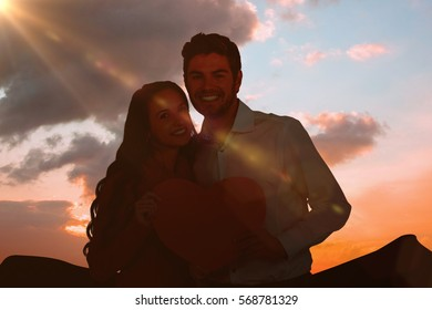 Happy couple holding paper heart against cloudy sky