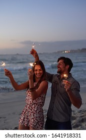happy couple holding sparklers celebrating new years eve on beach at sunset with sparkle firework