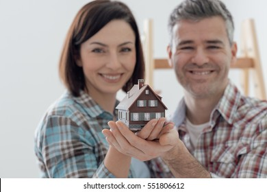 Happy couple holding their dream house in their hands, real estate and home insurance concept