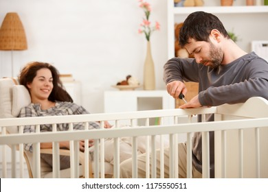 Happy couple at home expecting baby, man fixing crib, smiling. Focus on man.