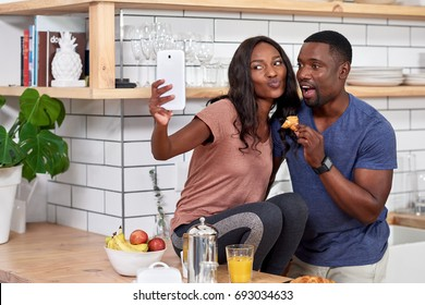 Happy couple at home having breakfast together, laughing smiling together loving relationship taking selfie