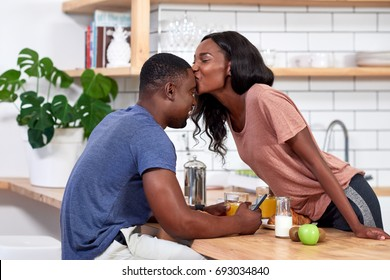 Happy couple at home having breakfast together, laughing smiling together loving relationship