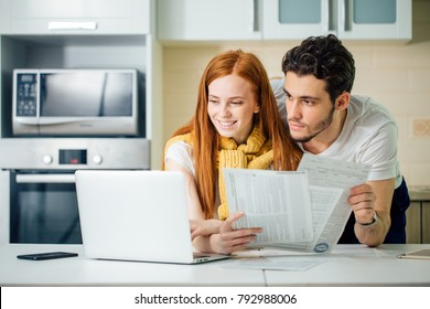 Happy couple at home paying bills with laptop and looking screen