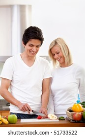 Happy couple at home with a table full of healthy food