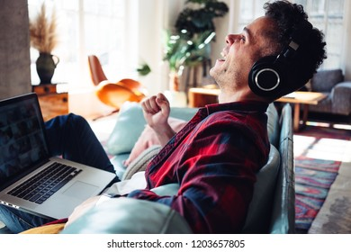 Happy couple at home. Young husband watching laptop and wearing headphones, sitting on the couch