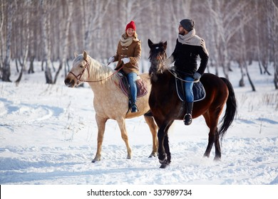 Happy couple horse riding in the forest