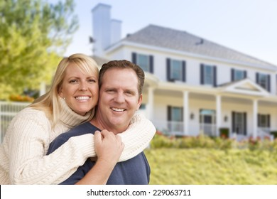 Happy Couple Hugging in Front of Beautiful House.