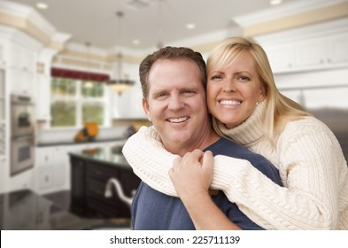 Happy Couple Hugging Inside Beautiful Custom Kitchen.