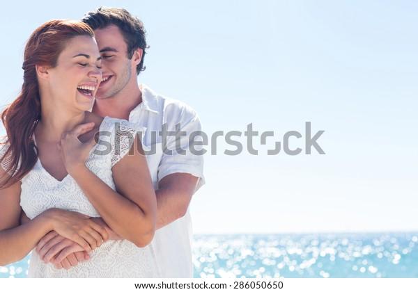 ビーチで抱き合って笑う幸せな夫婦