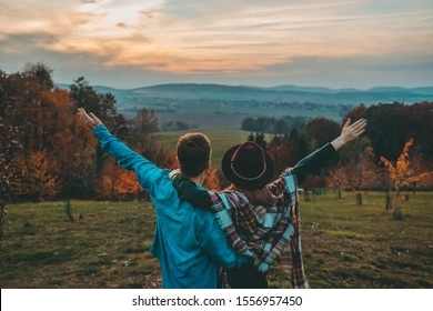 Happy Couple Hugging on Scenic Autumn Hills at Sunset. Young Hipster Man and Woman in romantic relationship enjoying fall outdoors at dusk. Cinematic shot.