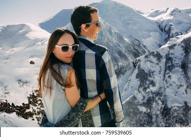 Happy couple hugging outdoor at winter mountains, two in love over natural wintertime landscape background, romantic Christmas vacation holidays. Man and woman wearing sunglasses fun on weekends.