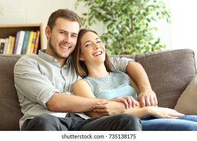Happy couple hugging and posing looking at camera sitting on a couch at home