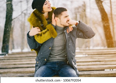 happy couple hugging and sitting on a bench in the park on a sunny winter day