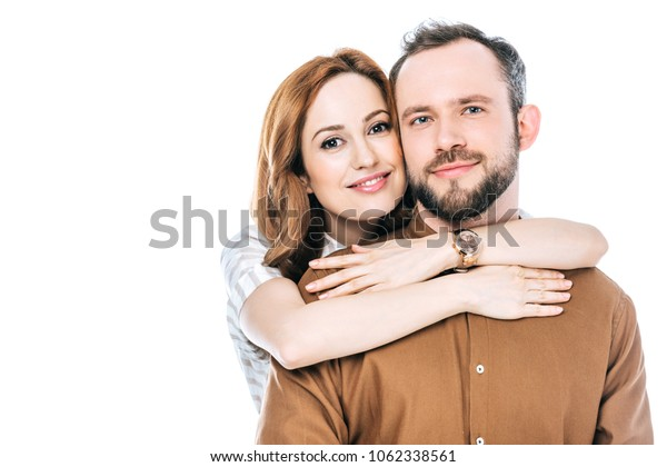 happy couple hugging and smiling at camera isolated on white