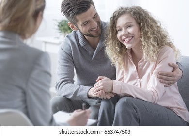 Happy couple hugging and smiling during therapy session