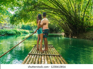 Happy couple hugging and standing on bamboo raft, whilst on  cruise along Martha Brae river. Shot on romantic vacation in Montego Bay, Jamaica, Caribbean