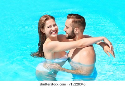 Happy couple hugging in swimming pool