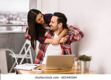Happy couple hugging and working together at home