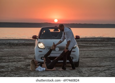 happy couple into sunset behind small car