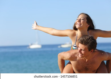 Happy couple joking piggibacking celebrating summer vacation on the beach
