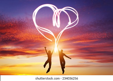 Happy couple jump together and make a heart symbol of light manifesting their love. Romantic sunset sky, Valentines Day.