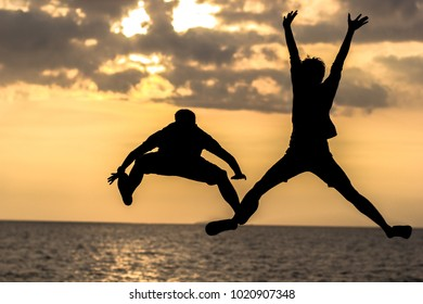 Happy couple jumping on the beach at sunset,family summer holidays or my friend.