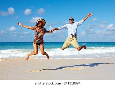 Happy couple jumping on the beach. Crazy vacation