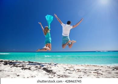Happy couple jumping with outstretched arms on beach and enjoying their caribbean vacation. Back view
