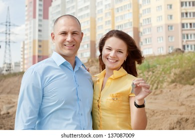 Happy couple with key against new brick house