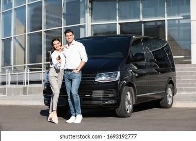 Happy couple with key near car on city street. Buying new auto