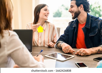 Happy couple with key of the new apartment . The woman is having the key to a house. Key with a keychain in the shape of the house. Agent estate doing the contract. Focus on keychain - Image