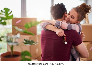 Happy couple with keys of new apartment