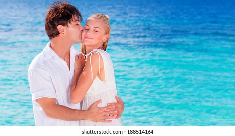 Happy couple kissing on the beach, young family in love spending honeymoon vacation on an islands, cheerful active young people having fun at summer travels, joy of life concept