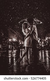 happy couple kissing under  the rain