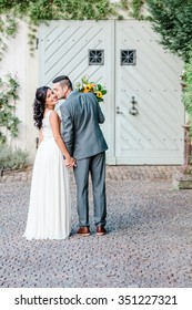 Happy couple kissing at the wedding day in front of the door. Full body portrait.