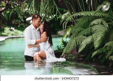 Happy couple kissing while relaxing in outdoor spa swimming pool surrounded with lush tropical greenery of Ubud, Bali. Luxury spa and wellness vacation retreat concept.