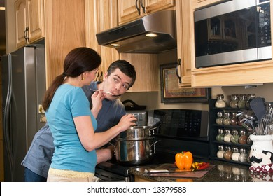 Happy couple in the kitchen near a counter, microwave, and a chopped pepper. She is letting him taste the food she is cooking on the stove.  Horizontally framed photograph